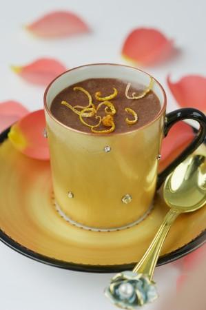 花びら: デザートはすぐ近くにありますゴールドと黒のコーヒー カップの静物をオレンジとチョコレートのムース オレンジのバラの花の花びらに囲まれて上にオレンジの皮でいっぱい。