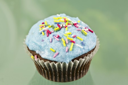 buttercream: A chocolate cupcake decorated with blue buttercream icing and sugar strands LANG_EVOIMAGES