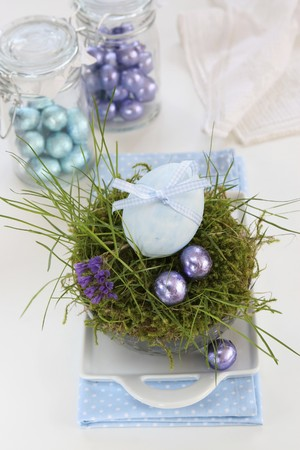 sweet grasses: An egg decorated with a ribbon and chocolate eggs in an Easter nest made of moss and grass