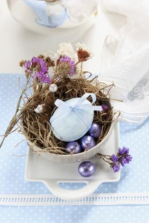 fiori secchi: Un uovo decorato con un nastro, fiori secchi e le uova di cioccolato in un nido di Pasqua fatta di muschio e di erba LANG_EVOIMAGES