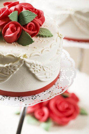 doiley: A wedding cake with red marzipan roses