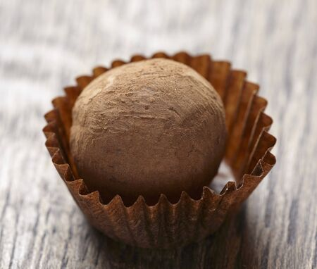chocolate truffle: Close up of chocolate truffle on brown wooden table LANG_EVOIMAGES