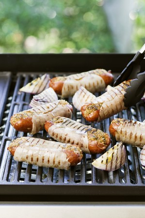 grill tongs sausage: Stuffed sausages wrapped in ham on the barbecue LANG_EVOIMAGES