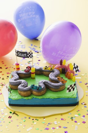 childs birthday party: A childs birthday cake (a racing track) and balloons