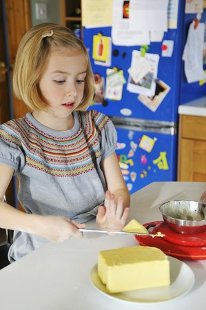 10 to 12 year olds: A girl in a kitchen cutting a piece of butter LANG_EVOIMAGES