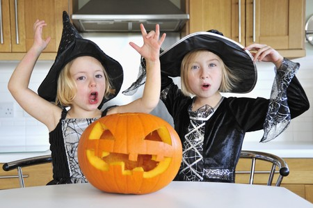 10 to 12 year olds: Two girls in the kitchen with a Halloween pumpkin