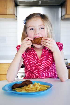 10 to 12 year olds: A little girl eating a chicken leg with chips