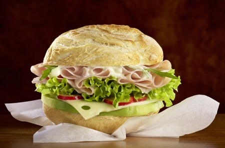 topped: A roll filled with cheese, ham and salad