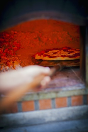 woodfired: A pizza being pushed in to a hot, glowing wood-fired oven