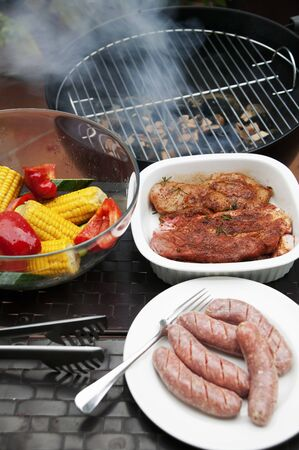 grill tongs sausage: Marinated pork steaks, sausages and vegetables in front of a hot barbecue LANG_EVOIMAGES