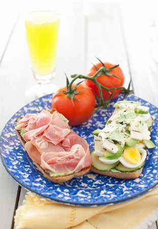 several breads: An Open Ham, Egg, Cucumber and Avocado Sandwich on a Blue and White Plate; Tomatoes