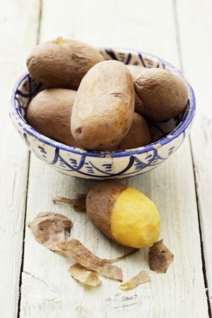side order: Potatoes cooked in their skins, in and next to a bowl