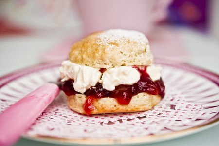 doiley: A scone with cream and strawberry jam on a doily with a teacup in the background