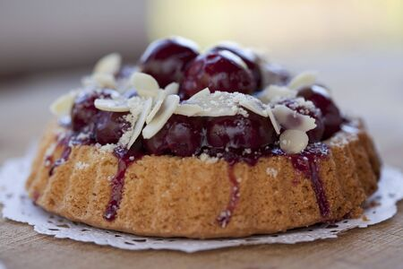 doiley: Individual cherry-topped cake with sliced almonds LANG_EVOIMAGES