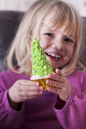 solo  christmas: A young girl holding a Christmas tree cupcake in both hands LANG_EVOIMAGES