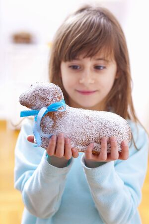 casual clothing 12 year old: A girl holding a cake in the shape of an Easter lamb LANG_EVOIMAGES