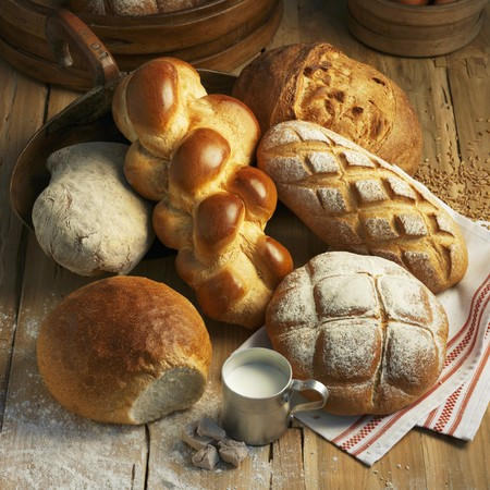 several breads: Assorted types of bread and a Hefezopf (sweet bread from southern Germany) on a rustic wooden surface