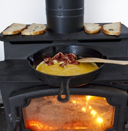 wood burning stove: Eggs and Bacon Cooking in a Cast Iron Skillet on a Wood Burning Stove; Bread Toasting on the Stove LANG_EVOIMAGES