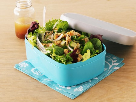 tupperware: Mixed leaf salad with smoked salmon in a lunch box with a jar of dressing