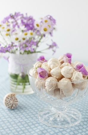 花びら: ガラス足ボウル花色、花びらのメレンゲ クッキーの完全な背景の花の花瓶
