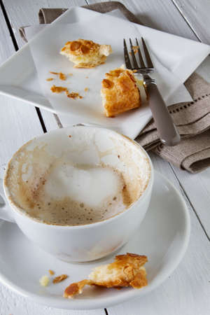 turnover: Remains of milk foam in a cappuccino cup and the last pieces of an apple turnover LANG_EVOIMAGES