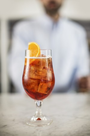 spritz: A glass of Aperol Spritz on a marble table LANG_EVOIMAGES
