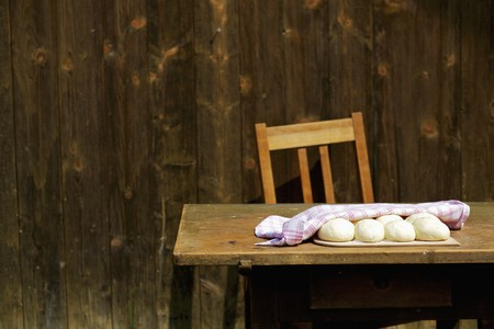 farmyards: Dough balls covered with a tea towel on a wooden table outside a wooden cabin