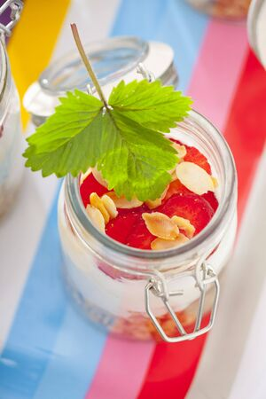 rolled oats: A jar containing ingredients for muesli: rolled oats, vanilla yoghurt and strawberries