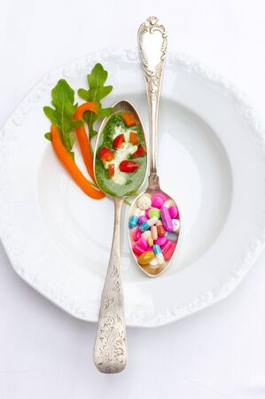 anti ageing: A spoonful of herb sauce with peppers and a spoonful of vitamin pills LANG_EVOIMAGES