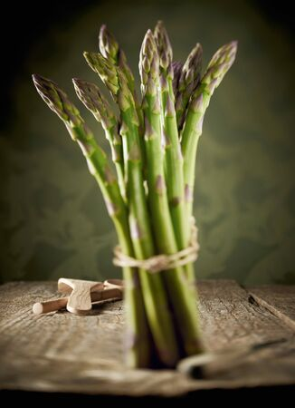 bunched: Green asparagus, bunched, on a wooden table