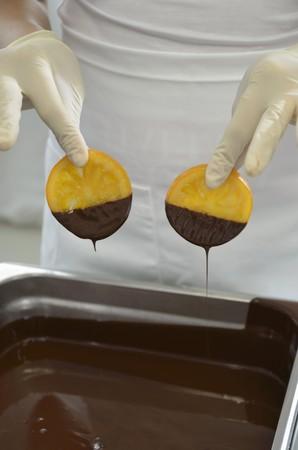 chocolate derretido: Un chocolatero sumergiendo las rodajas de naranja confitada en chocolate derretido