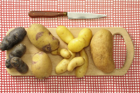 fingerling: Assorted types of potato on a chopping board LANG_EVOIMAGES