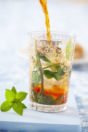 teas: Iced tea being poured into a glass with ice cubes and mint