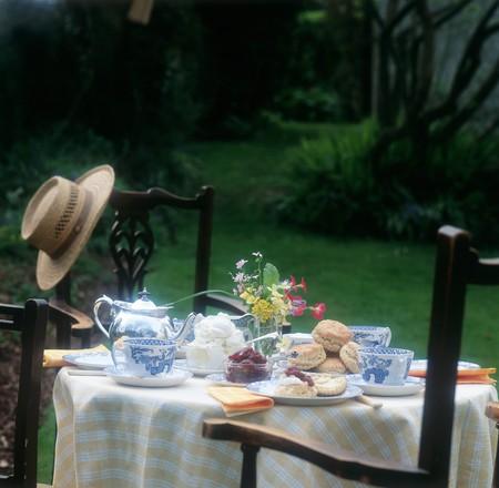 uk cuisine: Cream tea - table set outside (with hat) Devon