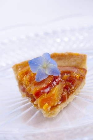orange tart: A slice of orange tart with a blue hydrangea flower LANG_EVOIMAGES
