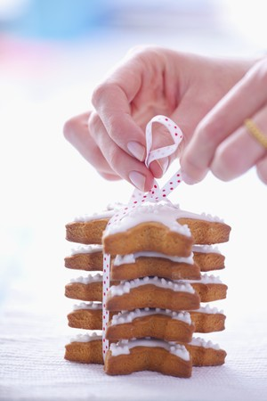 solo  christmas: Woman tiding a pile of gingerbread stars garnished with icing
