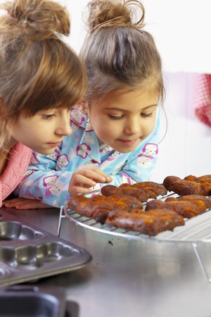 carrot cakes: Two girls looking at freshly baked carrot cakes