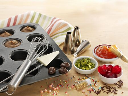 jimmies: A muffin tray with batter, baking utensils and toppings LANG_EVOIMAGES