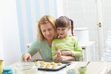 jam biscuits: Una madre e figlia con una teglia con i biscotti crudi marmellata