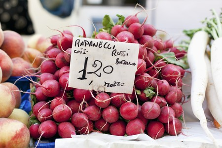 bunched: A pile of radishes at the market with a price sign