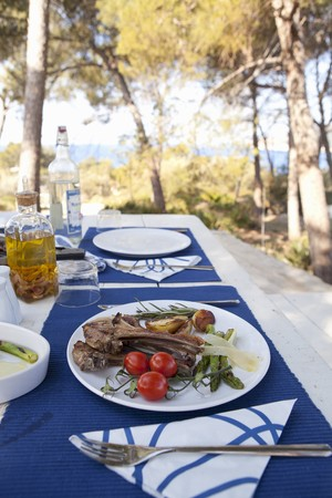 barbecues: Grilled lamb chops with green asparagus, cherry tomatoes and roast potatoes on a table outdoors LANG_EVOIMAGES