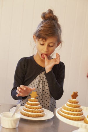 solo  christmas: A girl decorating Christmas trees made from stacked Lebkuchen (spiced soft gingerbread from Germany)