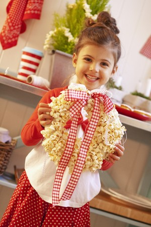 3 5 years: A small girl holding a Christmas wreath made from popcorn