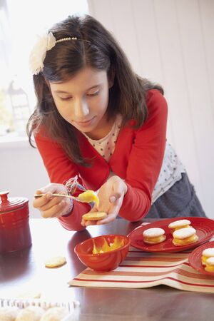 solo  christmas: A girl filling biscuits with lemon curd