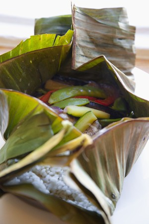 cocozelle: Rice, courgette, peas, peppers and onions in a banana leaf