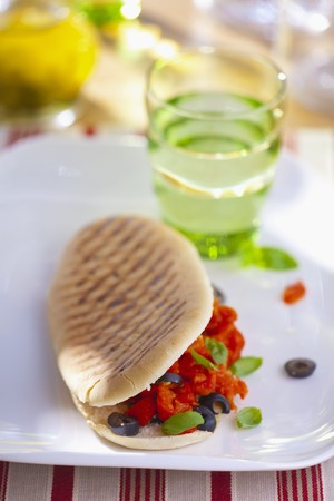 qs: A grilled sandwich with tomatoes, black olives and basil LANG_EVOIMAGES