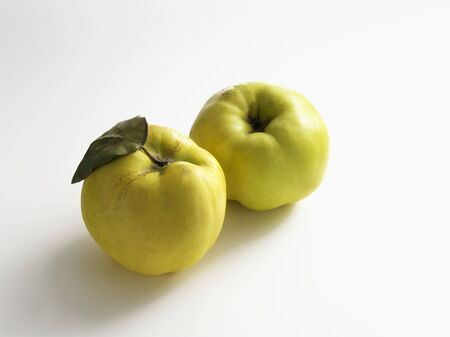 quinces: Two quinces on a white surface