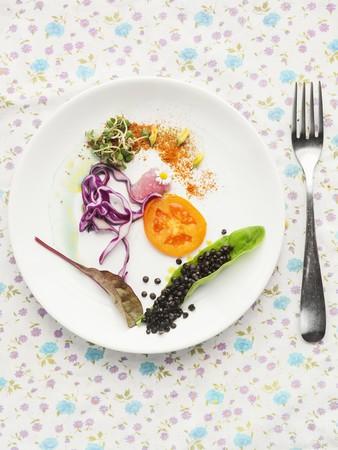 plato de ensalada: Un plato de ensalada con tomate, col roja, brotes comestibles y lentejas negras