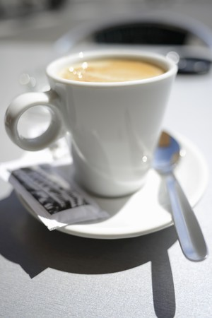 hot coffees: Latte in a white cup with a packet of sugar and a spoon