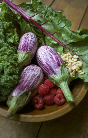 pine kernels: Striped aubergines, raspberries, salad and pine nuts in a wooden bowl